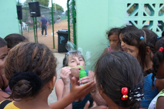 Vermont parent Wendy Agnew blows bubbles for a group of Cuban kids near the stadium.