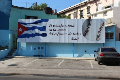 "A billboard outside the Estadio Latinoamericano reading: ""The triumph will be the sum of the efforts of all"" when translated into English."