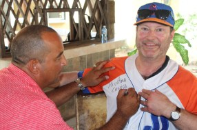 Vermont Coach Tom Simon gets a jersey signed by Yosvani Aragon, a former star Cuban pitcher. The jersey is the final one he ever wore, and was given to Simon as a gift.