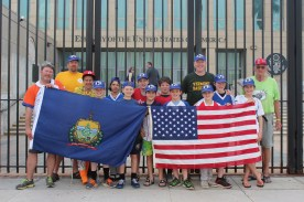 The team poses for a photo with the Vermont and United States flags outside the U.S. Embassy in Havana.