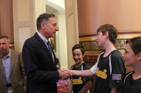 Vermont Governor Peter Shumlin shakes the hand of player Tate Agnew.