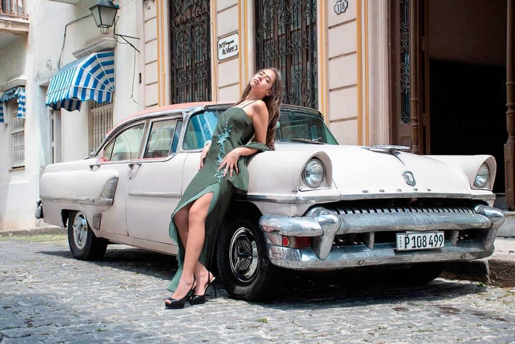 fotografia de quinceañera rubia con vestido verde apoyada sobre un auto clasico blanco en la habana