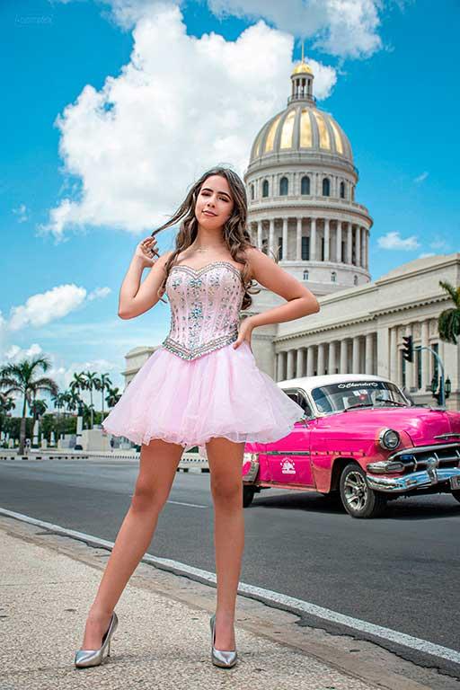 fotografia profesional a muchacha cumpliendo quince años con un vestido rosado frfenta al capitolio de la habana y un auto clasico rosado en verano