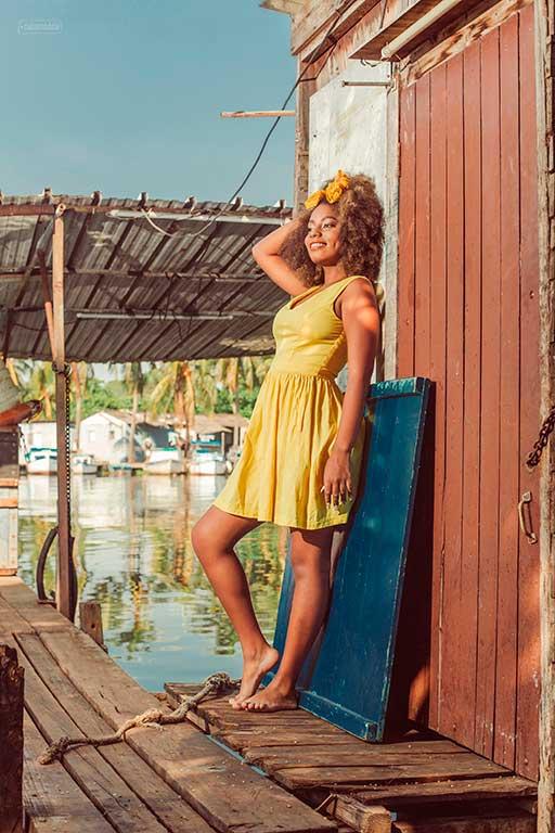 fotografía profesional a quinceañera cubana en un puerto, con un vestido amarillo y luciendo un hermoso cabello al estilo afro