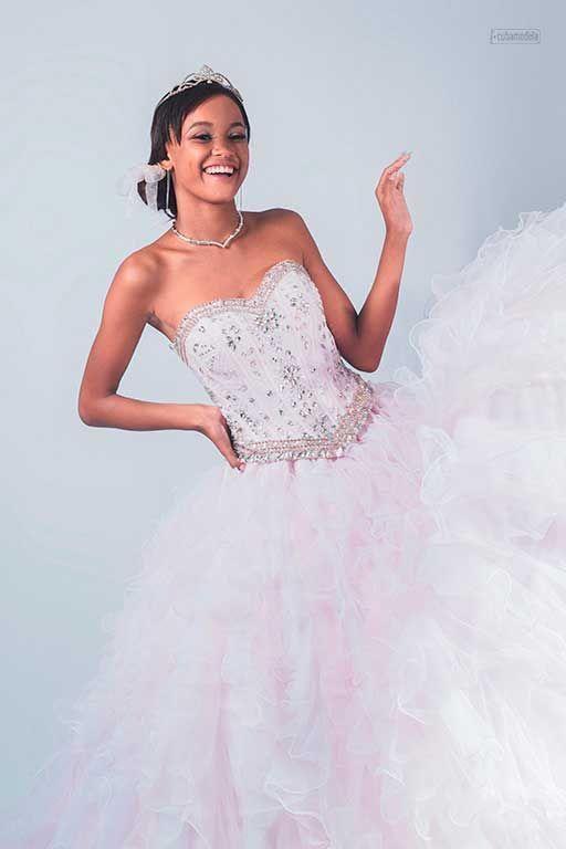 fotografia en el estudio de fotografia cubano de Cubamodela a quinceañera soriendo usando un vestido de vuelo blanco