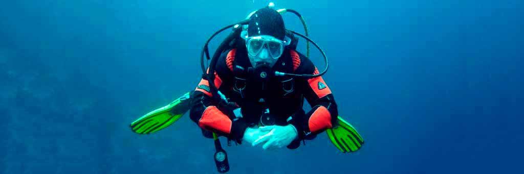 hombre buceando con traje de buzo debajo del mar azul