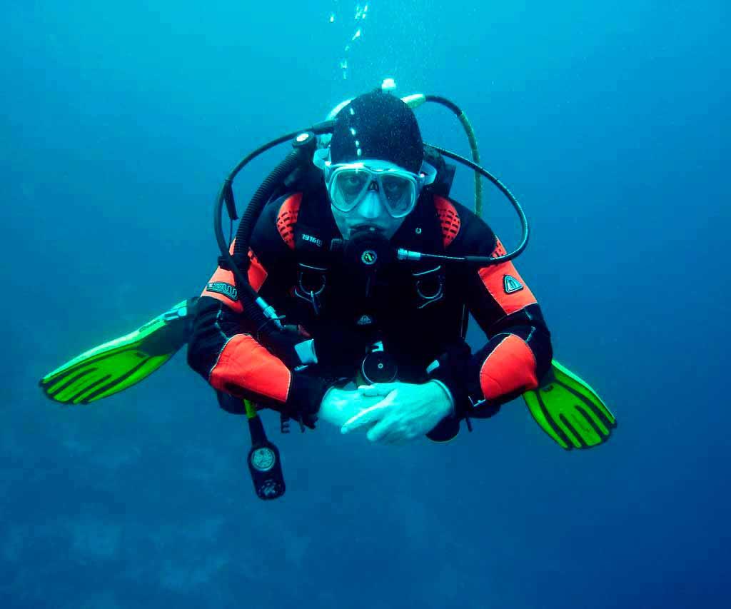 hombre beceando con traje de buzo debajo del mar azul