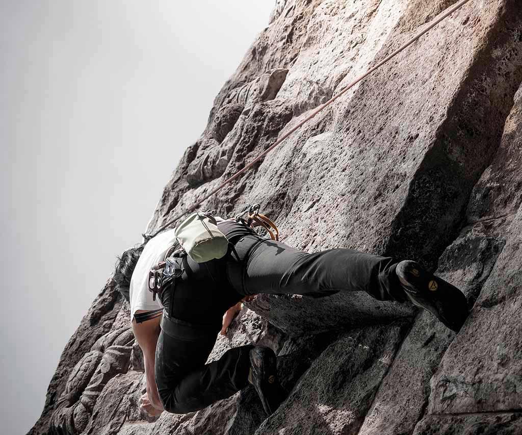 Hombre blanco encalando en montaña rocosa en un dia soleado