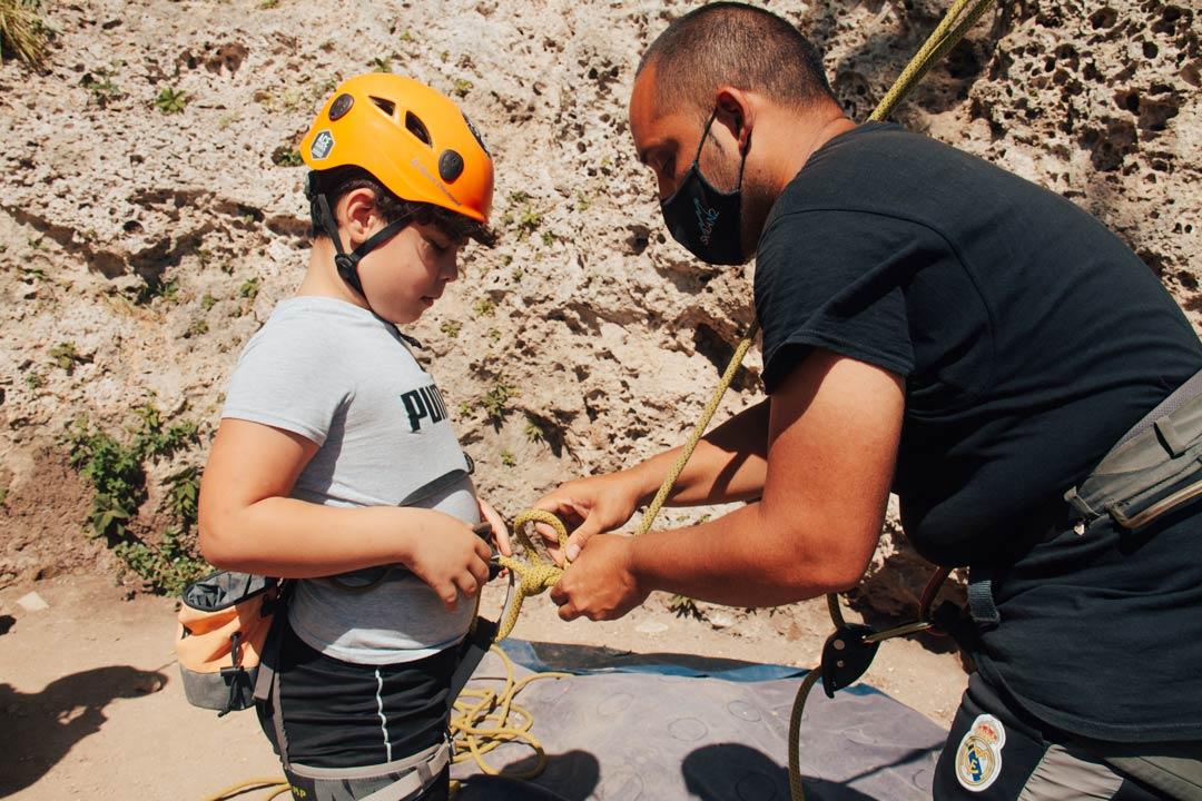 niño con arnes de pecho completo en la escalada deportiva modalidad top rope
