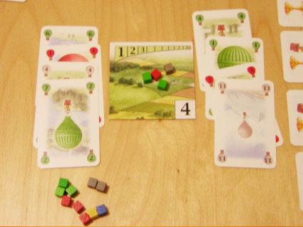 En esta situación, el jugador de la izquierda consigue la loseta, y con los cubos que gana más los acumulados previamente, puede reclamar dos trofeos, verde y gris. A continuación, el contrario quizá pueda reclamar algún trofeo.