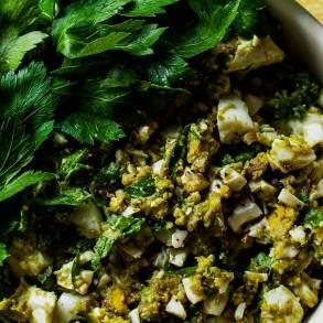 Bowl de ensalada de huevo perejil y aguacate con jugo de limón y pimienta