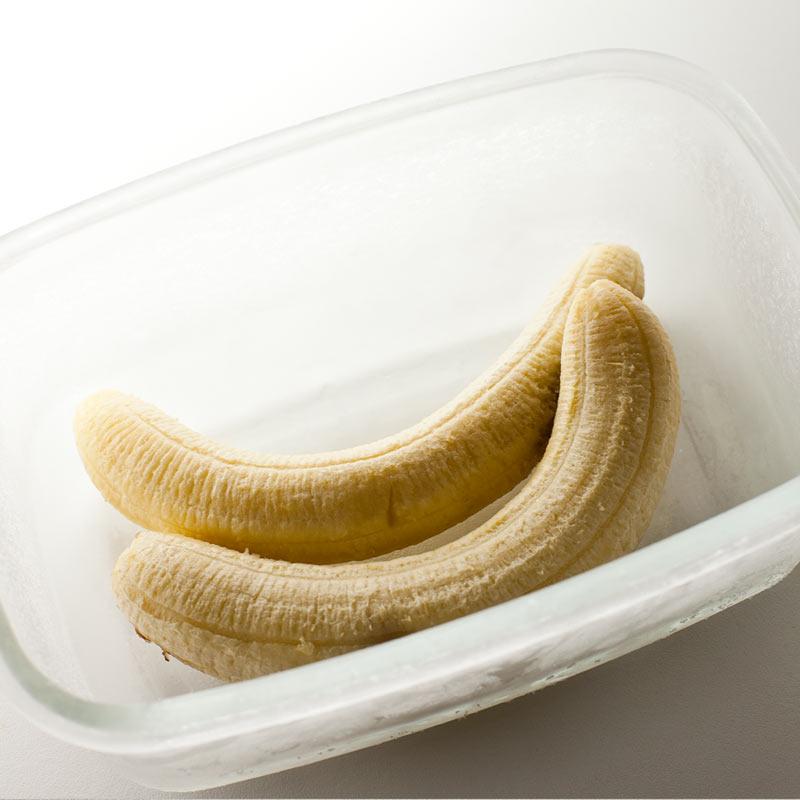 Plátanos congelados sin piel en recipiente de vidrio