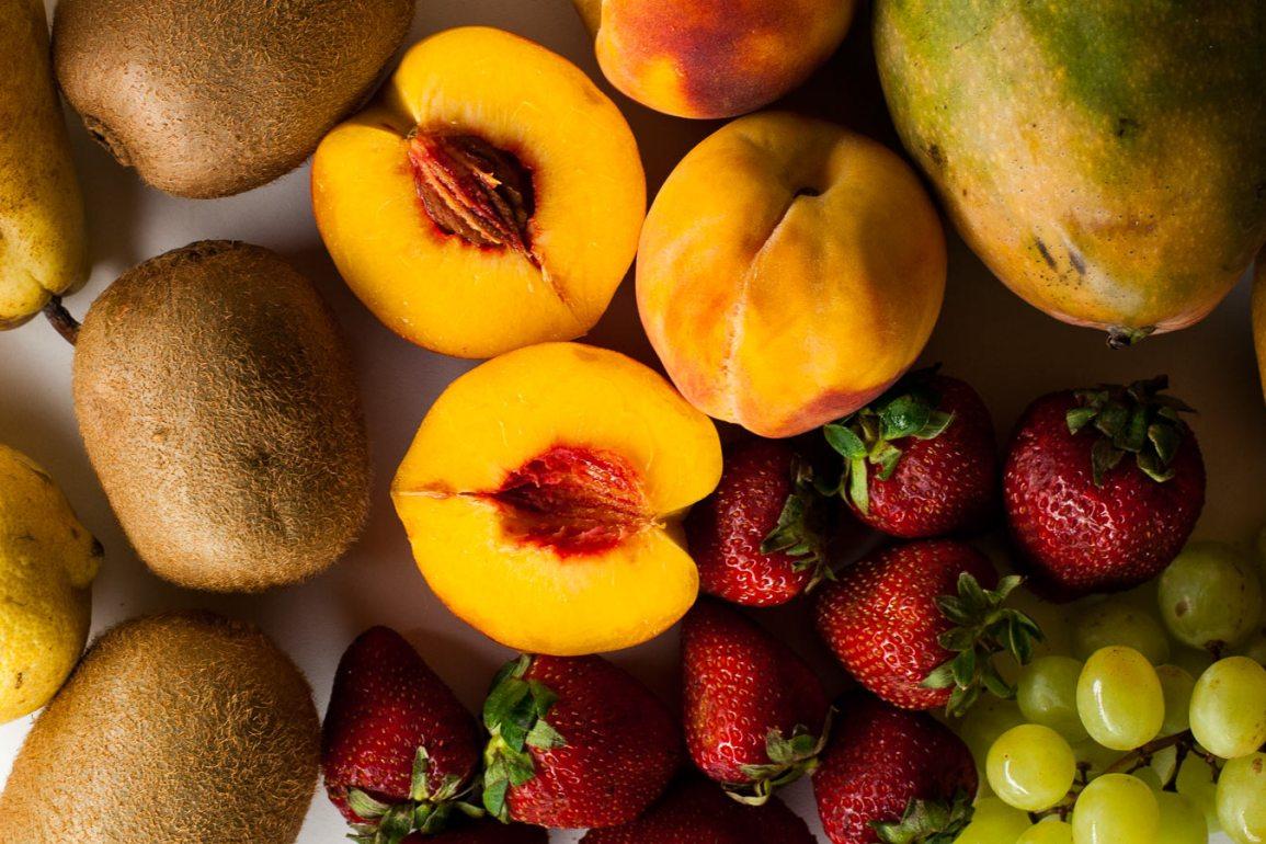 Melocotones, fresas, kiwis, mangos, limones, peras y kiwis sobre mesa blanca
