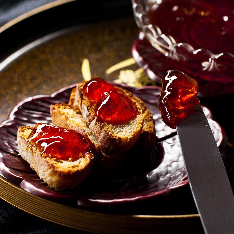 Tostadas untadas con jalea de membrillo junto con cuchillo de untar sobre bandeja