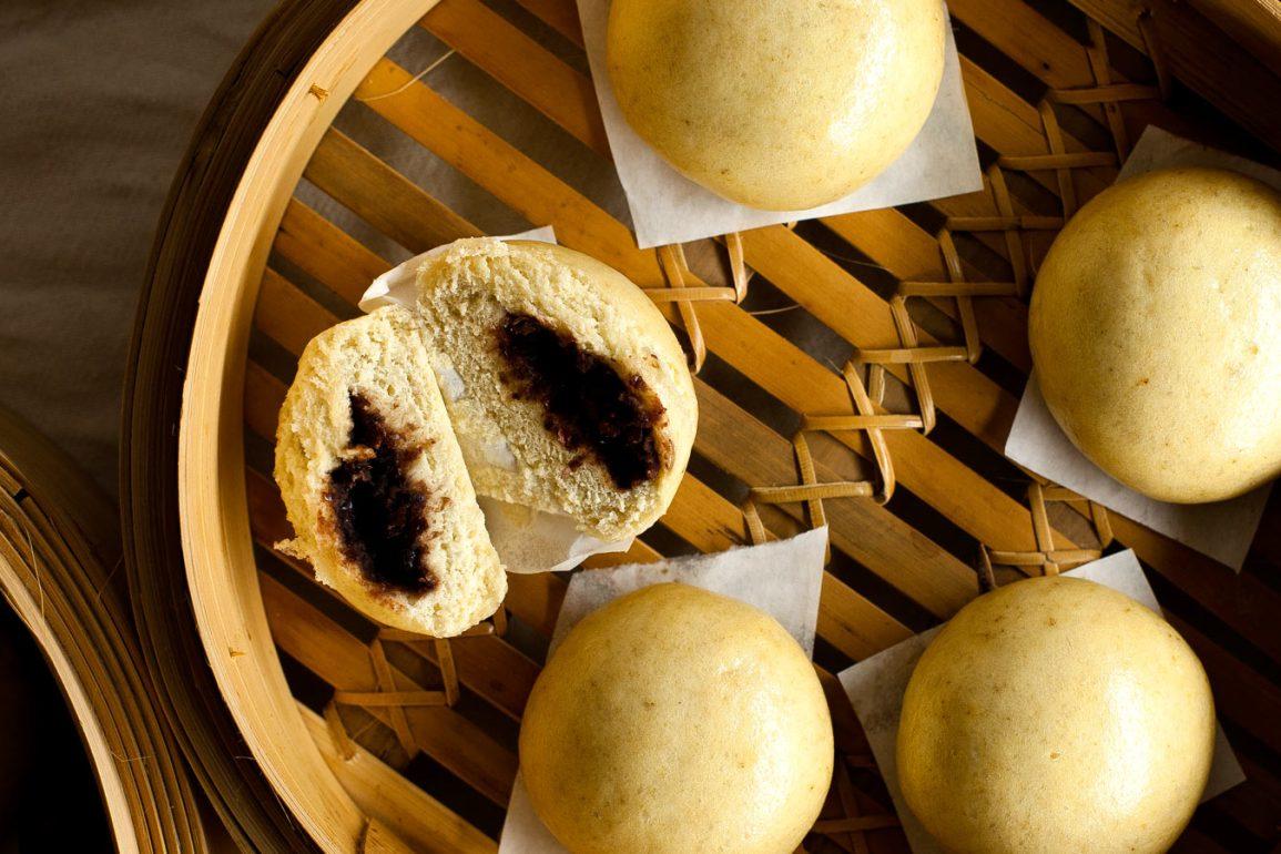 Manju pasteles cerrados y uno cortado a la mitad, sobre vaporera de bambú