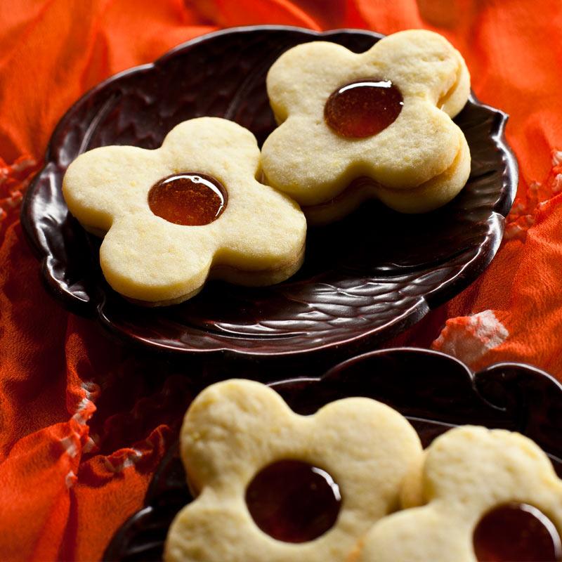 4 galletas de masa sablée en forma de flor sobre platos de laca