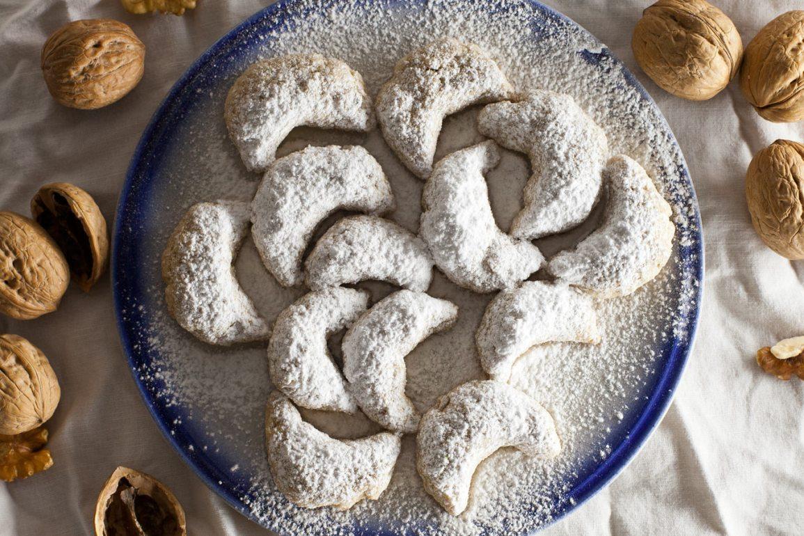 Galletas vanillekipferl espolvoreadas con azúcar glass sobre plato con cáscara de nueces alrededor