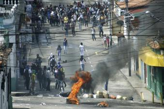 Students block a street as they clash with national guards during a protest against the government in San Cristobal