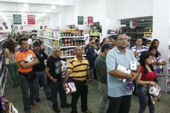 People line up to buy basic goods at a supermarket in San Cristobal