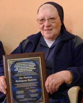 r (Sister) Patricia of the Hermanitas de la Caridad (Sisters of Charity) with the plaque she was awarded for service to the community.