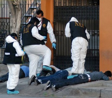 Police examine bodies after a shoot-out between drug cartel members.