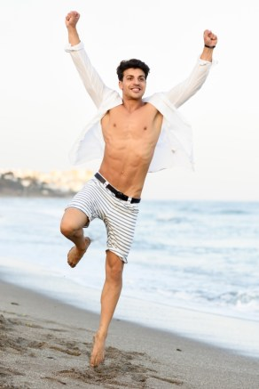 man-with-open-shirt-on-the-beach-and-a-raised-leg_1139-576