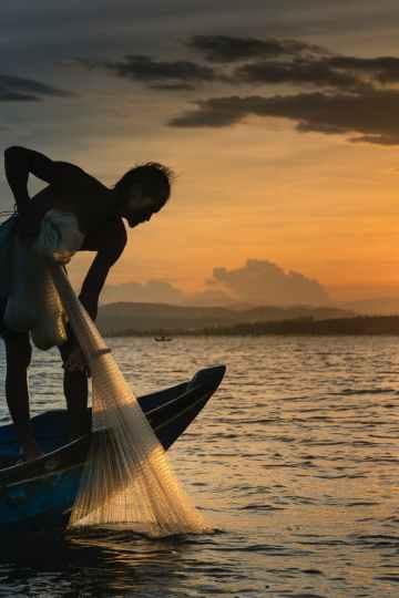 man on boat holding white mesh fishing net