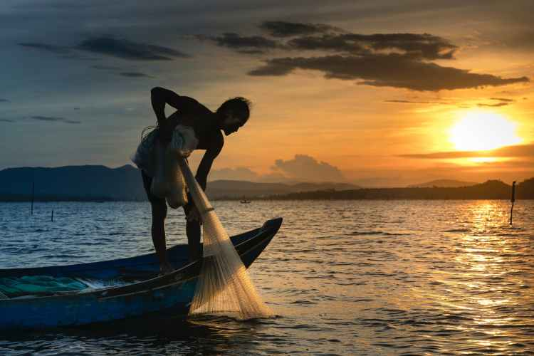 man on boat holding white mesh fishing net