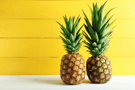 53496712 - ripe pineapples on a white wooden table