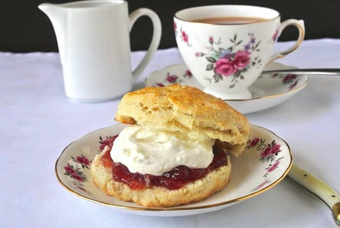 A flowered plate with a scone, jam and clotted cream and a cup of tea in the background