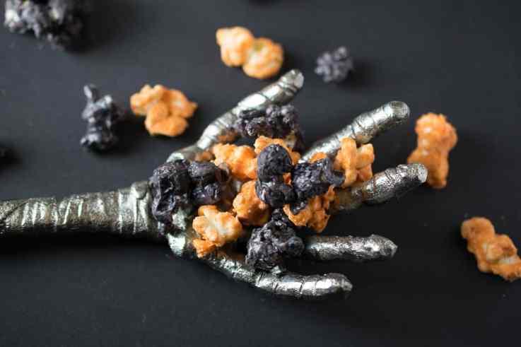 A scary metal mummy hand holding Halloween popcorn