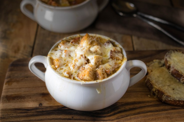 French onion soup in a white bowl with a side of cheese toast
