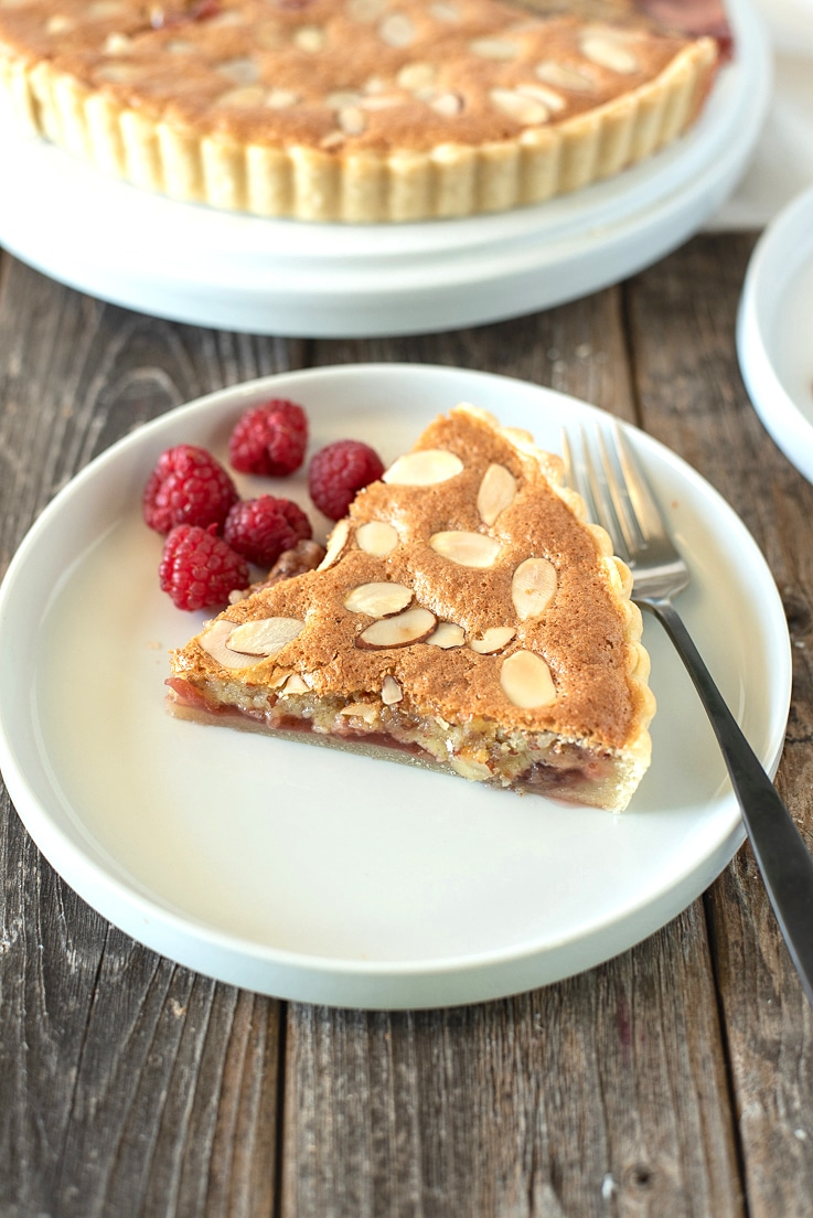 A slice of bakewell tart on a place showing the strawberry jam layer with a fork and raspberries