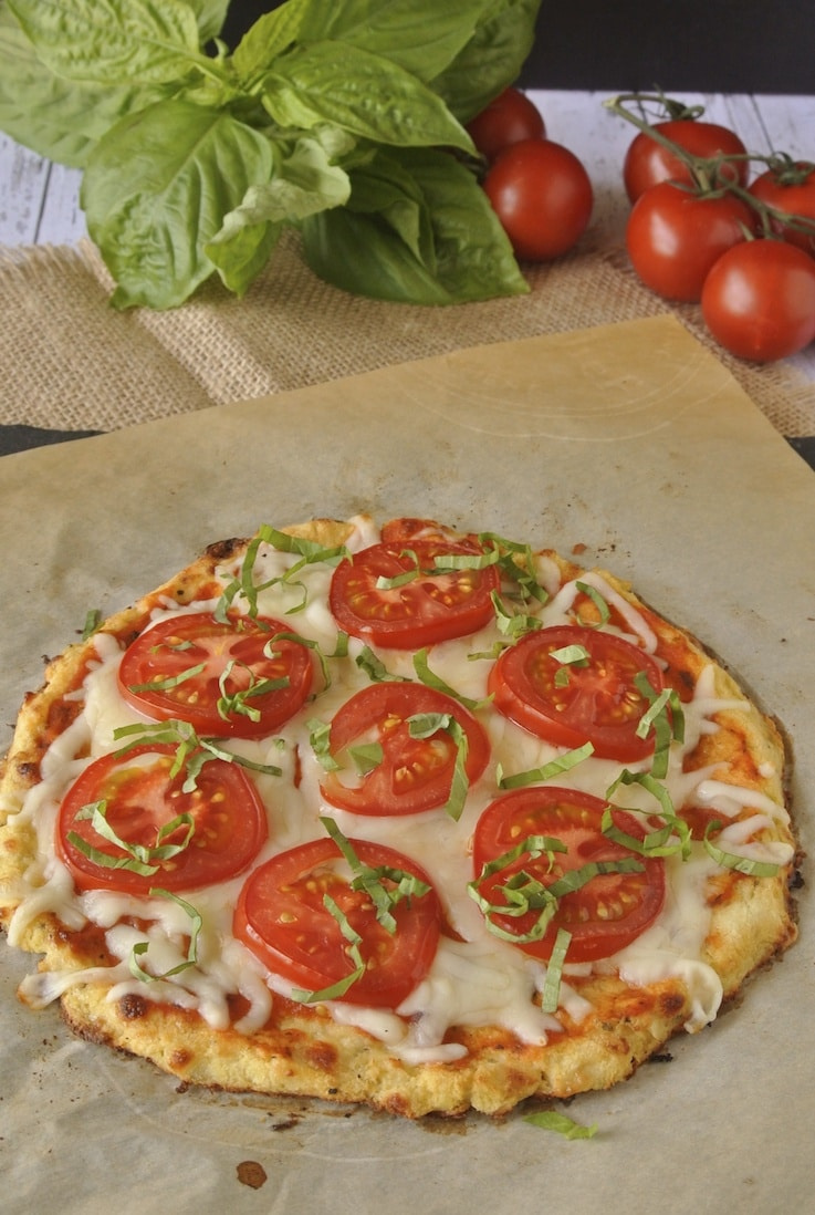 Cauliflower Crust Tomato Basil Pizza fresh out of the oven with a bunch of fresh basil and tomatoes in background