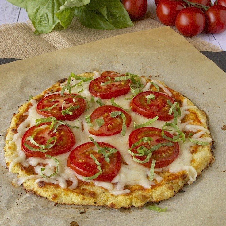 Cauliflower Crust Tomato Basil Pizza ready to be sliced