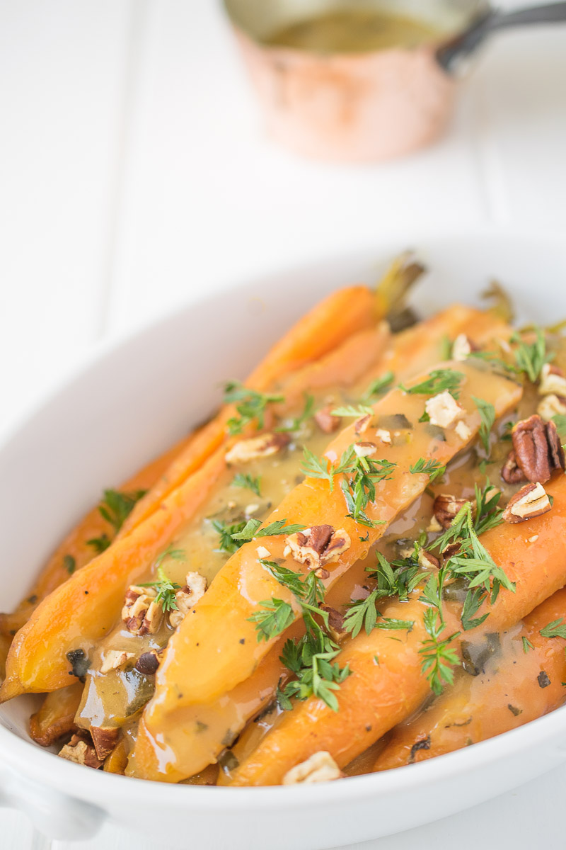 A closeup showing the delicious garnishes on top of the bright orange carrots