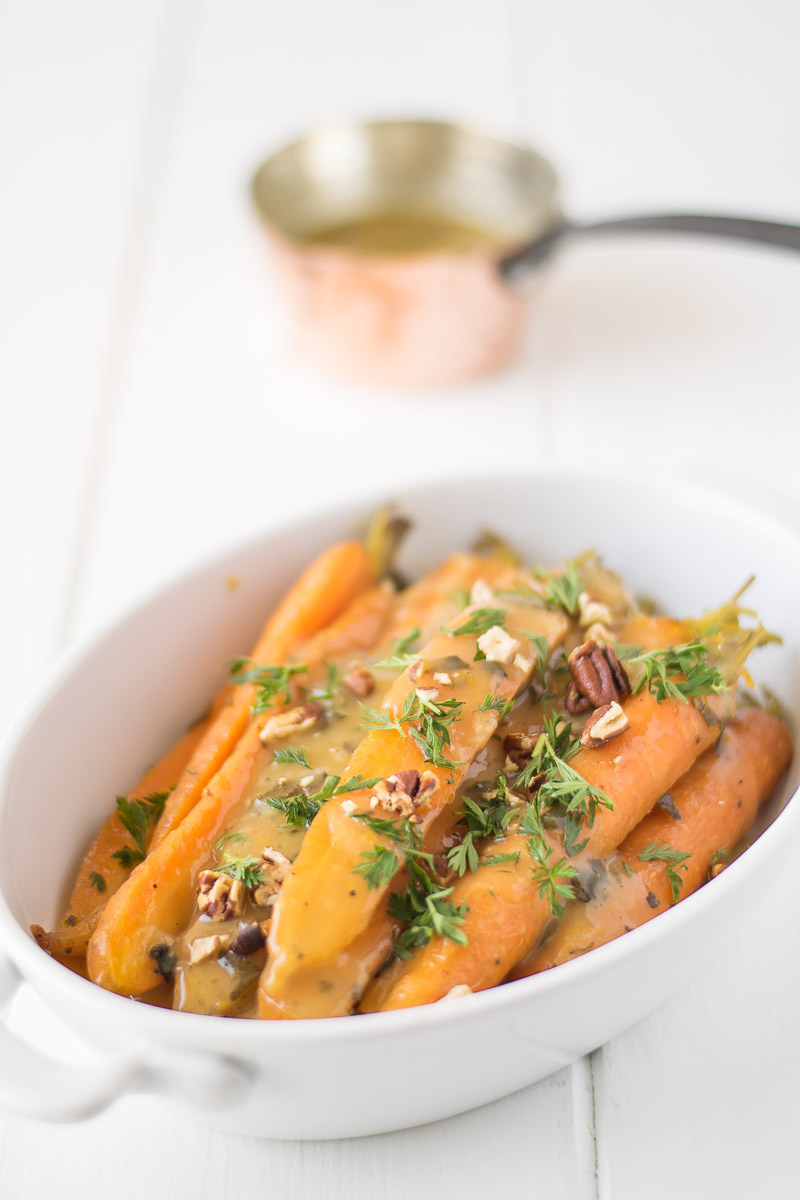 Crockpot orange, honey and herb glazed carrots garnished with greens in a white oval dish