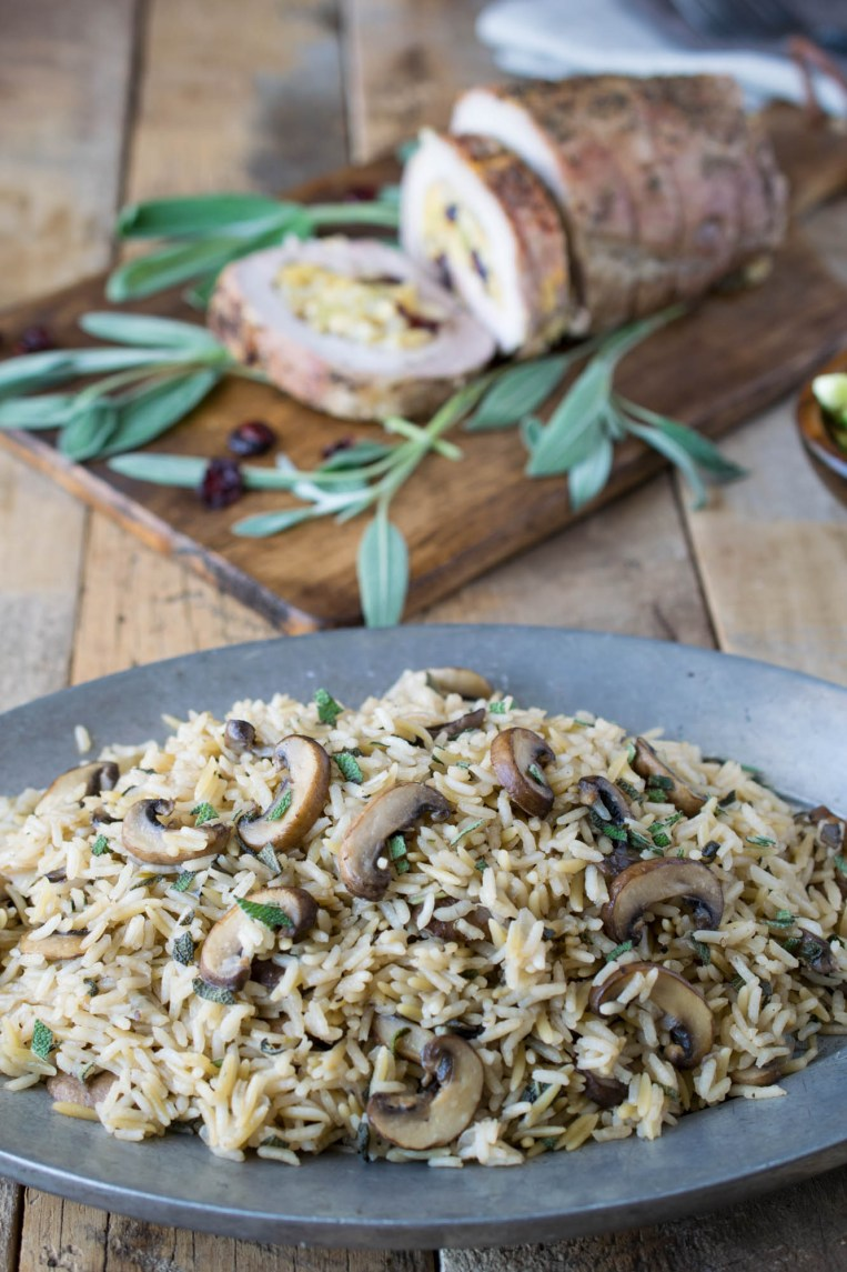 A plate of mushroom and sage rice pilaf in the foreground with stuffed pork in the background
