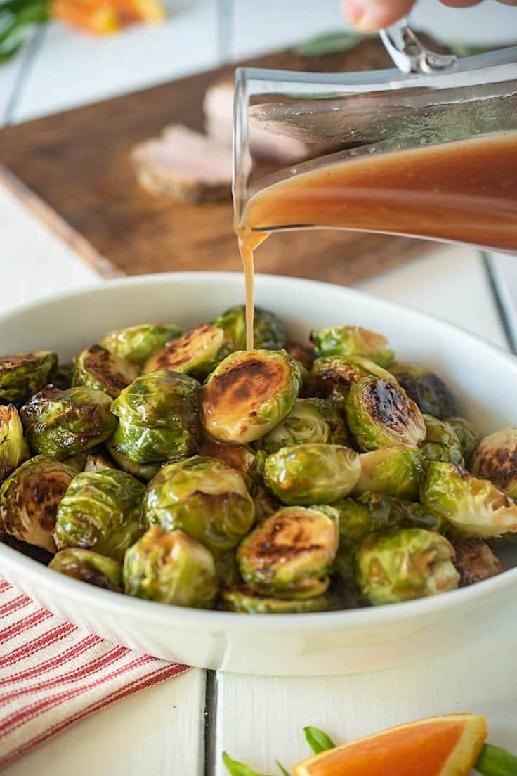 Cranberry glaze being drizzled over roasted Brussels sprouts