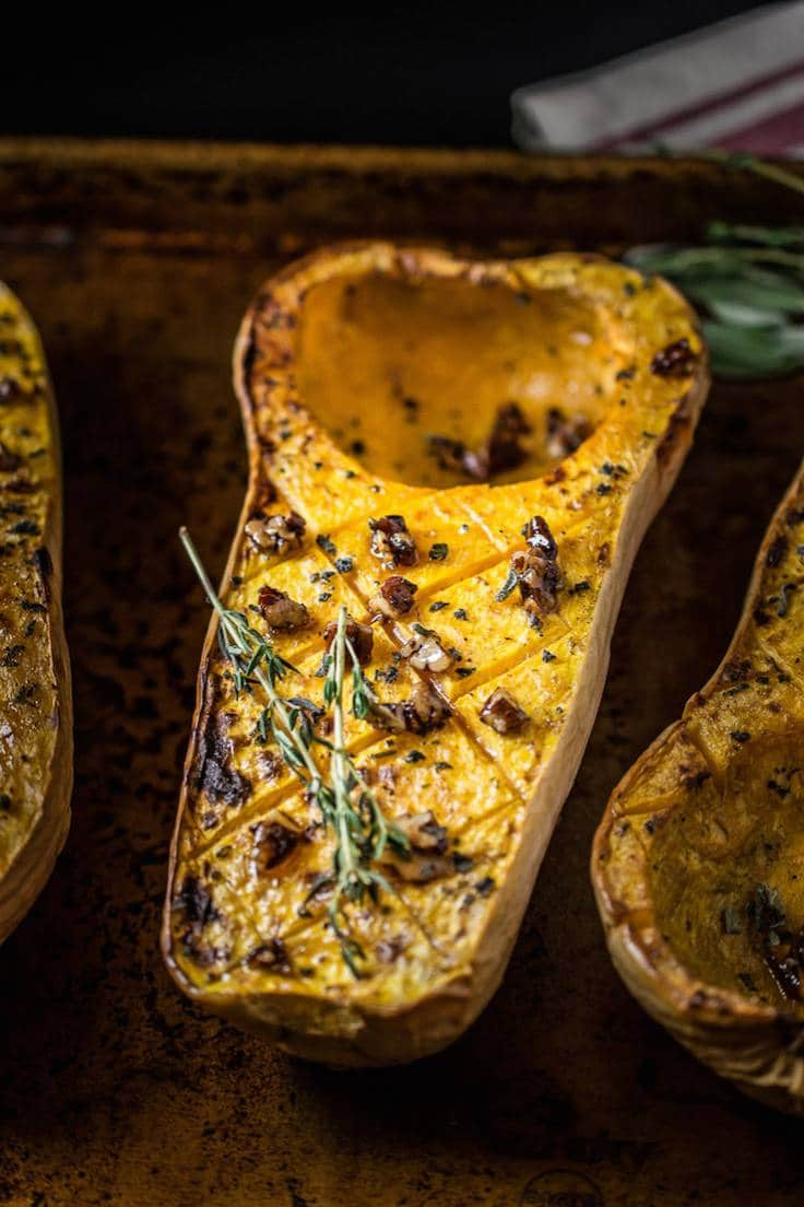 Half of a butternut squash, roasted with maple pecans on a baking sheet