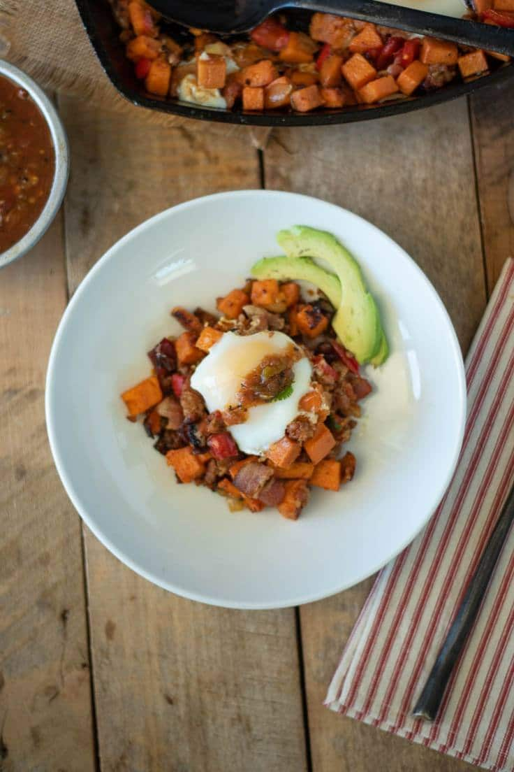 The breakfast skillet is served on a white plate topped with salsa and fresh avocado