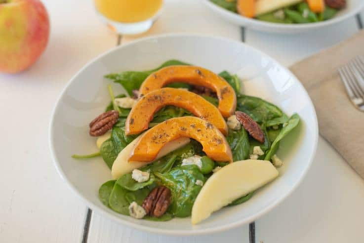Sliced roasted butternut squash over spinach with sliced apples and pecans in a white bowl