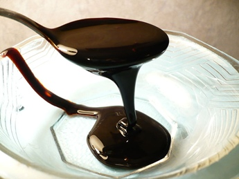 blackstrap molasses being poured from spoon