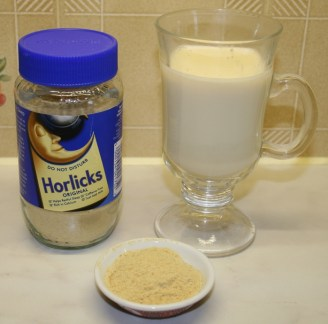 A Jar of Horlick's Malted Milk with some malted milk powder in a dish