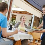waiter serving young couple in small italian restaurant