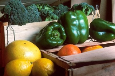 crate of oranges, green bell peppers, and broccoli