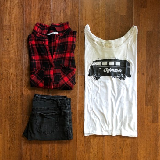 A pair of jeans, a tang-top shirt, and a red flannel are laid out on the floor for display.