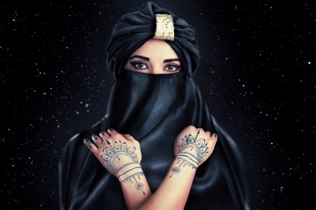 A beautiful woman wearing a turban. She has tattoos on her hands.