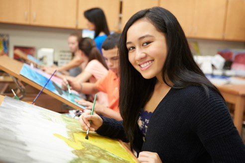 A photo of a female high school student painting in art class.