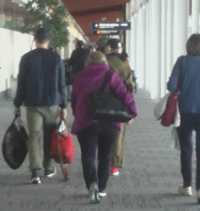 Scarlett lleva una gorrita está vestida de verde militar y zapatillas rojas y su novio a la izquierda llevando un bolso negro y otro rojo